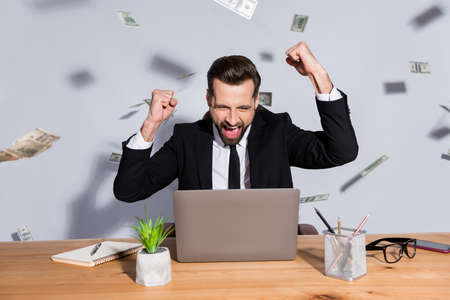 Photo of handsome crazy business guy notebook table usa bucks fall rich chief success startup income raise fists celebrate wear blazer shirt tie suit sit chair isolated grey background