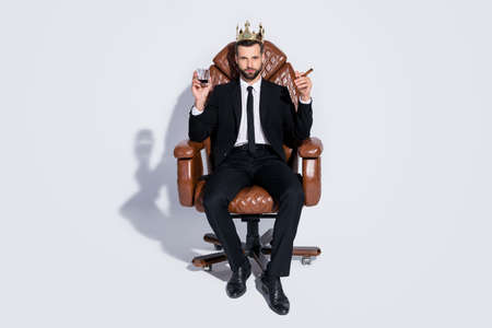 Full body photo of handsome business guy sit office chair hold whiskey glass cuban cigar luxury chief golden crown wear black blazer pants tie shirt shoes suit isolated grey background Фото со стока