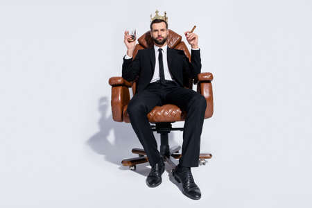 Full body low below angle view photo of handsome business guy sit chair hold rum glass cuban cigar chief wear crown black blazer pants tie shirt shoes suit isolated grey background