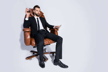 Full length photo of handsome business guy sit chair hold pack money dollars drink luxury expensive scotch ready pay wear black blazer pants tie shirt shoes suit isolated grey background