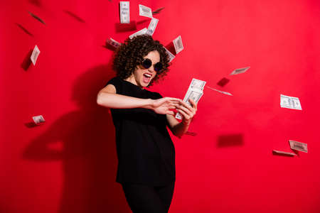 Photo portrait of crazy girl throwing money in air isolated on vivid red colored background Фото со стока
