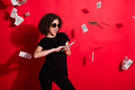 Photo portrait of woman throwing money in air isolated on vivid red colored background