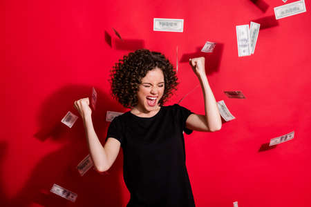 Photo of curly hairstyle girl scream closed eyes open mouth yes won black t-shirt isolated on red color background Фото со стока