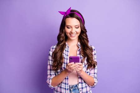 Portrait of her nice attractive focused cheerful wavy-haired girl wear checked shirt using device chatting isolated bright vivid shine vibrant violet lilac pastel color background
