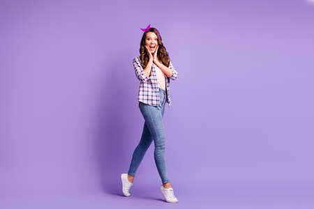 Full length profile photo of lady open mouth tiptoes wear checkered shirt headband jeans sneakers isolated violet color background Stock Photo