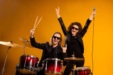 Photo of rock group band cool guy play instruments beat drum sticks crazy attractive redhair girl sing mic popular song showing horns wear black leather outfit isolated yellow background