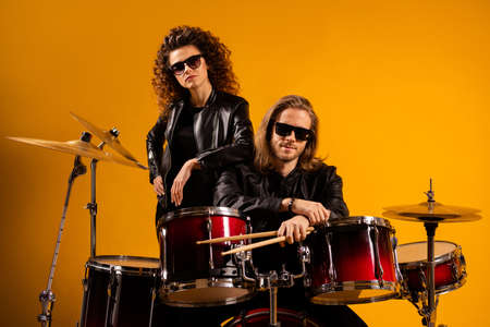 Portrait of nice attractive fashionable cool trendy couple playing professional concert leisure heavy metal genre dream profession isolated on bright vivid shine vibrant yellow color background