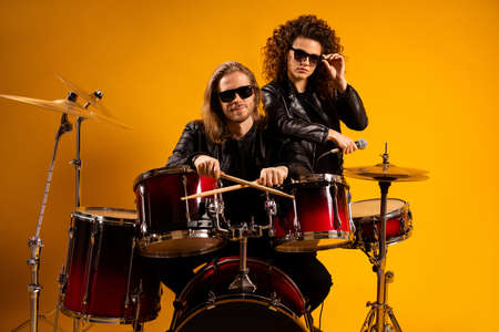 Portrait of his he her she nice attractive fashionable serious couple playing concert hobby leisure heavy metal genre rock roll gang isolated bright vivid shine vibrant yellow color background