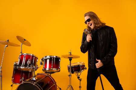 Portrait of famous punk singer guy use mic sing new composition in studio night club festival concert rehearsal wear black jacket sunglass isolated over bright shine color background