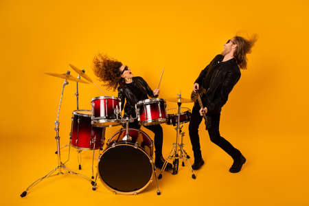 Full size photo crazy two people girlfriend boyfriend enjoy record studio composition ma play bass solo guitar girl drum scream wear leather outfit isolated bright shine color background Stok Fotoğraf
