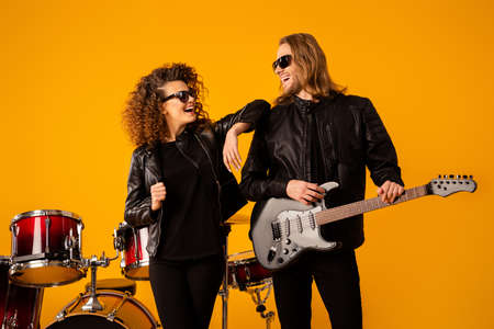 Portrait famous positive man woman rock group team man hold electric guitar enjoy performing new solo composition wear black leather jacket sunglass isolated bright shine color background