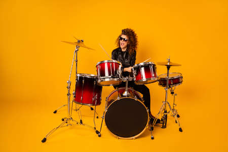 Full size photo of famous rocker redhair lady plays instruments beat hands drum sticks concert hobby bring money wear black leather clothes sun glasses isolated yellow background Stok Fotoğraf