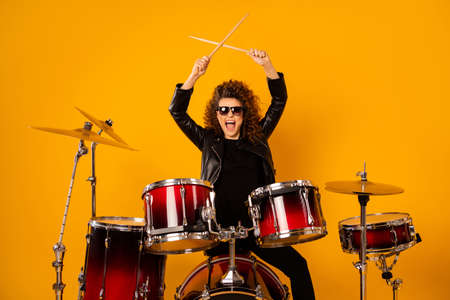 Photo of popular rocker redhair lady plays instruments beat raise hands drum sticks concert sound check repetition wear black leather outfit sun glasses isolated yellow background