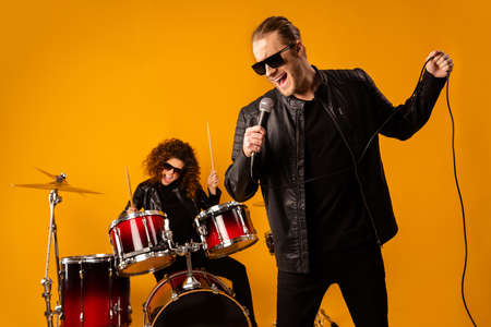 Photo of popular rock group redhair lady plays instruments beat drum sticks vocalist guy sings mic concert sound check repetition wear black leather outfit isolated yellow background Stok Fotoğraf