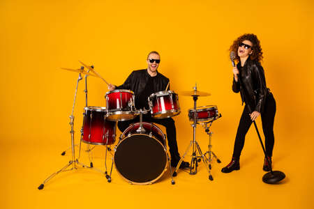 Full size photo of famous rock group guy plays instruments beat drum sticks attractive girl sings mic night club performance show concert wear black leather outfit isolated yellow background Stock Photo