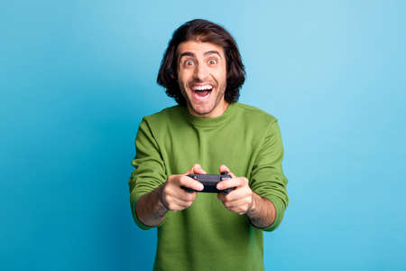Photo of excited gamer guy hold controller amazed open mouth wear green sweater isolated blue color background