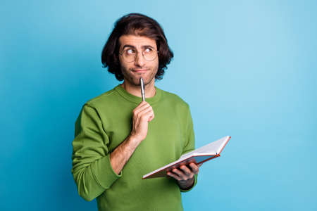 Photo of pensive guy hold copybook pen chin look empty space wear specs green sweater isolated blue color background Stock fotó