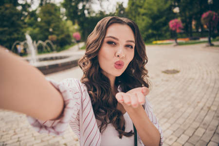 Photo portrait of female blogger with brunette curly hair taking selfie sending air kiss with plump pouted lips wearing casual clothes