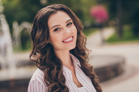 Photo portrait of young woman with brunette curly hair smiling wearing white casual shirt walking in green summer park Stock Photo
