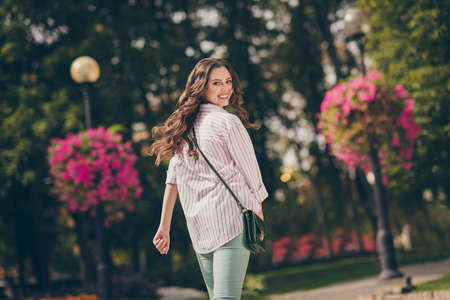 Rear behind view photo of pretty lady walk city central park active way life wear green jeans striped shirt shoulder bag outdoors