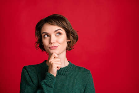 Portrait of nice hairdo lady arm on chin look empty space dark green pullover isolated on red color background