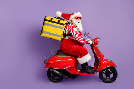 Photo of santa drive scooter fast food delivery wear backpack x-mas costume striped shirt cap specs isolated purple color background