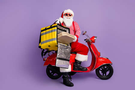 Photo of santa claus drive moped hold pizza box backpack wear x-mas costume striped shirt cap specs isolated purple color background