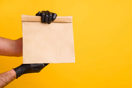 Cropped photo of delivery man arms hold takeout paper package wear black gloves isolated bright yellow color background Banque d'images