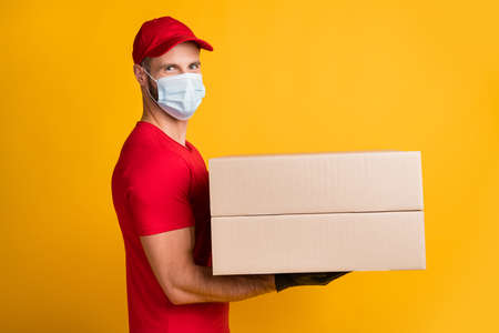 Profile photo of guy hold two big boxes wear gloves mask red t-shirt headwear isolated yellow color background