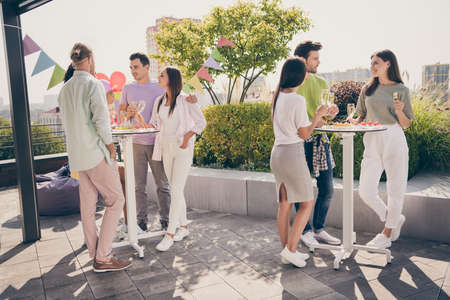Full body portrait of beautiful fellows stand around table hands hold champagne talk listen meeting restaurant outdoors Banque d'images