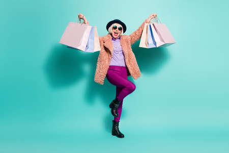 Photo of lucky old woman dressed vintage outerwear cap eyewear holding bags arms up isolated turquoise color background