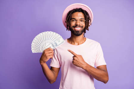 Photo of young afro handsome smiling positive man guy pointing finger hold money dollars isolated on purple color background