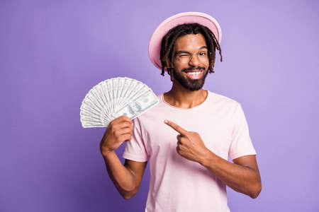 Photo of young handsome african happy smiling man guy wink eye point finger at dollars isolated on violet color background