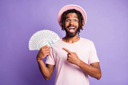 Photo of young happy excited afro man guy wear glasses pink t-shirt point finger at dollars isolated on purple color background