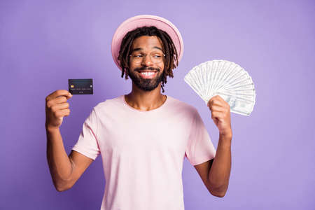 Photo of young afro smiling happy man guy wear pink t-shirt look in copyspace hold credit card dollars isolated on violet color background