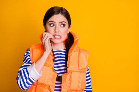 Close-up portrait of her she nice attractive pretty lovely nervous scared brown-haired girl wearing lifesaver biting nails worrying isolated over bright vivid shine vibrant yellow color background Stock Photo