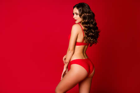 Profile rear behind view photo of seductive beauty curly lady slim body shapes look empty space wear brassiere panties lingerie underwear advertisement model isolated red color background