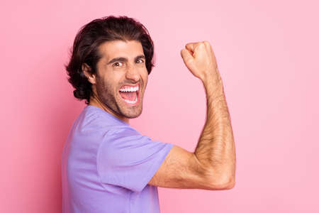 Photo of crazy bearded guy raise arm fist show muscle open mouth wear violet shirt isolated pastel pink color background 版權商用圖片
