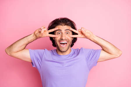 Photo of funky guy two hands show v-sign open mouth toothy smile wear purple t-shirt isolated pastel pink color background