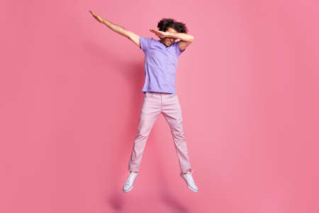 Full length photo of brown haired bristled sportive guy jump up dab cover eyes wear pink trousers isolated on pink color background Standard-Bild
