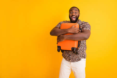 Portrait of his he nice handsome overjoyed crazy bearded cheerful cheery guy holding in hands hugging luggage departure exotic tour rest isolated on bright vivid shine vibrant yellow color background