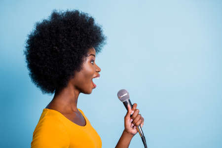Photo side profile portrait of pretty black skinned girl singing on microphone looking at copyspace isolated on bright blue color background