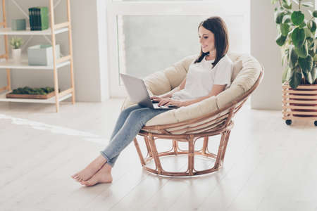 Full size photo of young lady sitting on wicker chair working laptop wear white t-shirt denim in house indoors 版權商用圖片