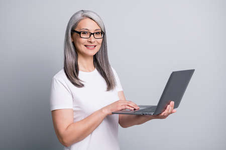 Photo of calm pensioner lady hold laptop toothy smile wear specs white t-shirt isolated grey color background 版權商用圖片