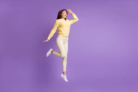 Full length photo portrait of girl looking in distance with head near forehead jumping up isolated on vivid violet colored background