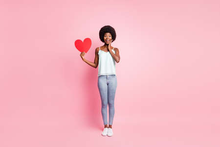 Full length photo of attractive curly hairdo person hand hold heart symbol sneakers isolated on pink color background