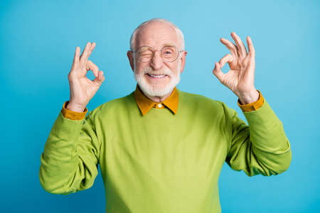 Photo of retired old man raise two hands show okey wink eye wear eyewear green pullover isolated blue color background