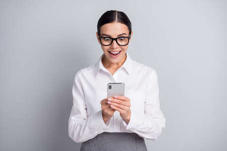 Photo of shocked worker girl hold smartphone open mouth wear specs white shirt isolated grey color background