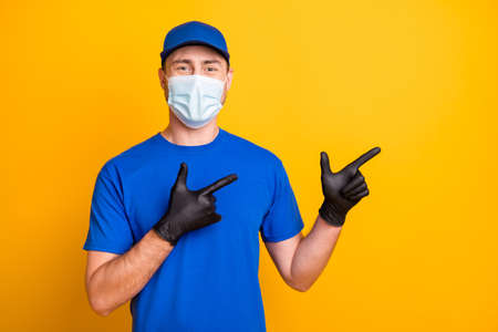 Photo of working guy wear cap direct fingers empty space healthcare cold safety mask isolated on yellow color background