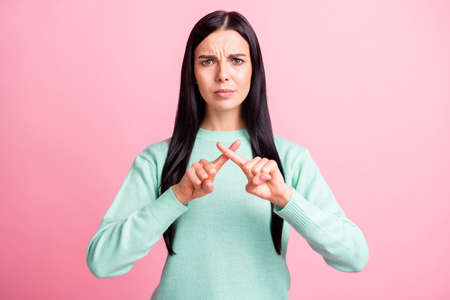 Photo portrait of upset woman showing cross with fingers isolated on pastel pink colored background Stock fotó